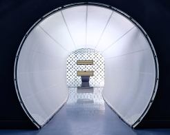 A white tunnel made of sail cloth continues the theme of a journey, as does the next room it leads to, where intentionally disorienting videos are projected on walls surrounding an oversized white Vuitton trunk
