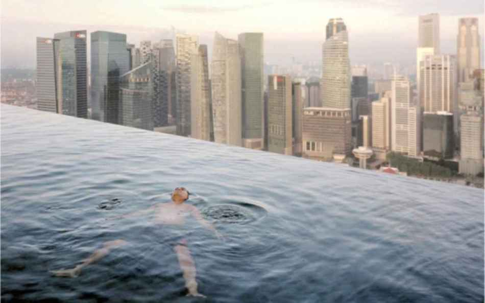 A man floats in the 57th-floor swimming pool of the Marina Bay Sands Hotel, with the skyline of the Singapore financial district behind him. 2013 © Paolo Woods & Gabriele Galimberti--INSTITUTE