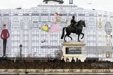 This picture taken on February 8, 2017, in Paris shows people walking past the French large department store of La Samaritaine under renovation and the Henri IV equestrian statue. / AFP / LIONEL February 08, 2017