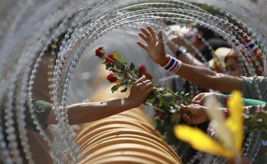 an-anti-government-protester-gives-a-rose-to-a-thai-soldier-at-the-defense-ministry-during-a-rally-in-bangkok
