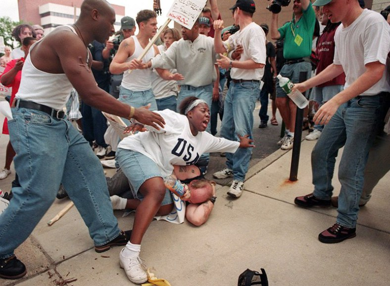 june-22-1996-e28093-then-18-year-old-keshia-thomas-of-ann-arbor-shields-a-man-wearing-a-confederate-t-shirt-from-an-angry-crowd-during-a-ku-klux-klan-rally-outside-ann-arbor_s-city-hall