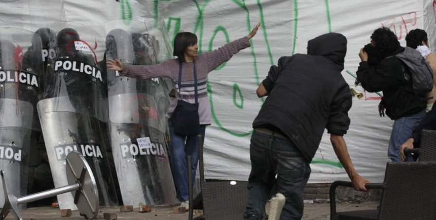woman-successfully-defends-a-group-of-cornered-riot-officers-from-angry-protesters-bogotc3a1-colombia-2013
