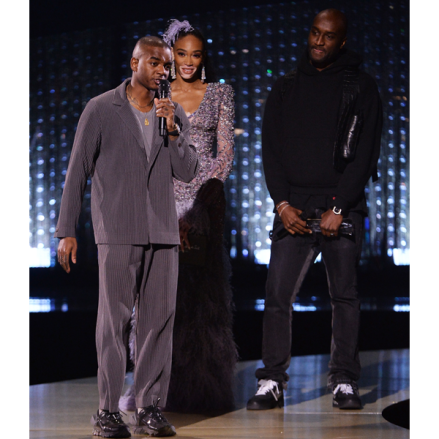 Designer Sam Ross of A Cold Wall* accepts the British Emergin Talent Menswear award from presenters Virgil Abloh and Winnie Harlow at The British Fashion Awards (2018).